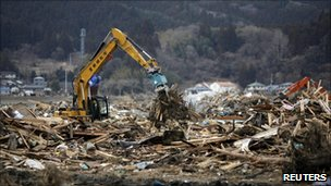 A bulldozer removes remains from destroyed houses