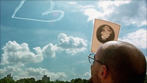 A man attending a memorial service for Diana, Princess of Wales in New York uses the program to shield his eyes from the sun as he watches a sky-writing aircraft sketch a heart in the sky