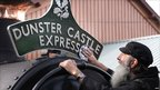 Man cleaning a Dunster Castle Express sign