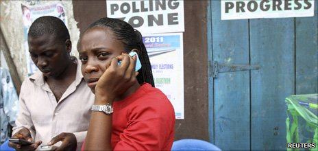 People on mobile phones at a polling station in Nigeria