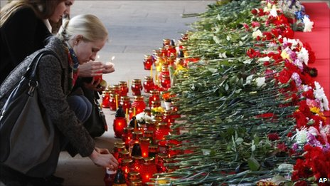 People light candles at a memorial to those killed in the metro station blast (12 April 2011)
