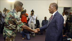Ivory Coast President Alassane Ouattara (r) shakes hands with General Philippe Mangou, chief of staff of former pro-Laurent Gbagbo Defence and Security Forces (FDS), at the Hotel du Golf in Abidjan, 12 April 2011.