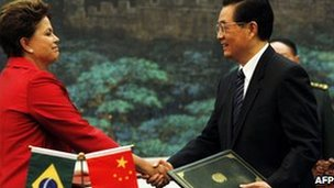 Brazilian President Dilma Rousseff shakes hands with her Chinese counterpart Hu Jintao 