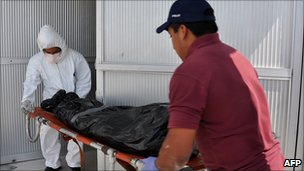 Forensic workers carry a body found in a mass grave in Matamoros, 11 April 2011