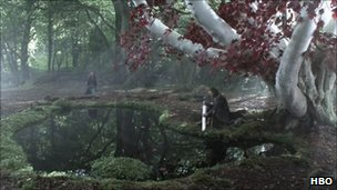 Sean Bean in armour kneeling at pond in forest