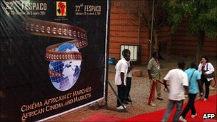 Visitors walk past the official poster of the 22nd Fespaco, Africa's biggest film festival