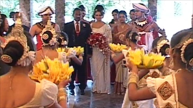 Sri Lankan bride is greeted by dancers at her wedding