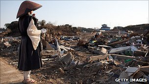 Buddist nun Jikou Yoshida prays at the site of the town of Minamisanriku, destroyed by the tsunami