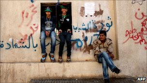 Libyan rebels sit on a wall covered in graffiti mocking Libya's leader Muammar Gaddafi, in the rebel-held city of Benghazi, eastern Libya on 14 April 2011
