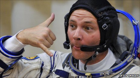 Doug Wheelock making a 'telephone' hand gesture