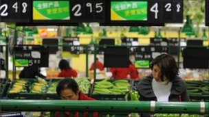 Chinese shoppers buy vegetables at a supermarket in Hefei