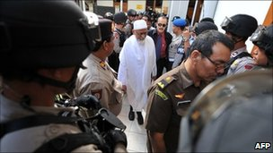 Armed anti-terror police commandos escort Abu Bakar Ba'asyir at Jakarta court on March 14, 2011