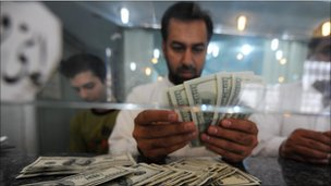 Pakistani money dealer counts US dollars notes at a money market in Islamabad