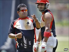 Canada cricketer Zubin Surkari (R) listens to team coach Pubudu Dassanayake during a training session in Bangalore, India