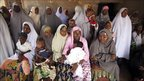 Muslim women wait under the shade to cast their vote at a polling station in Daura, Nigeria, 16 April 2011