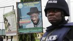 An armed police officer in riot gear stands guard in front of a poster of Nigerian incumbent President Goodluck Jonathan in Jonathan's home village of Otuoke, Bayelsa state, Nigeria, April 16, 2011