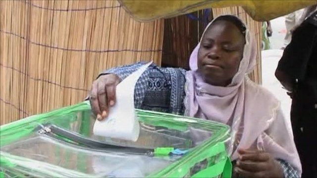 Woman posts ballot paper into box