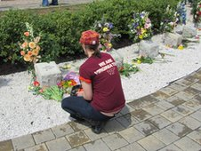 A Virginia Tech student kneeling in front of memorial stones
