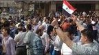 People gather during a demonstration in Homs, 18 April.