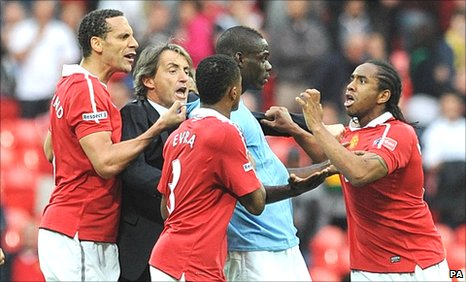 Mario Balotelli (centre) is confronted by United players Anderson (right) and Rio Ferdinand (left) and Patrice Evra (foreground), while City manager Roberto Mancini (second left) attempts to intervene