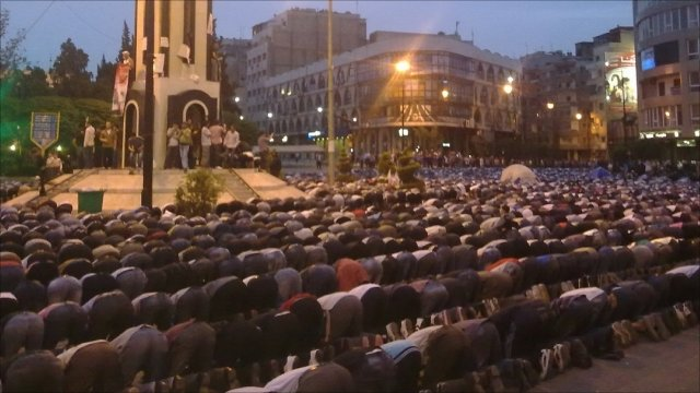 People praying in Homs
