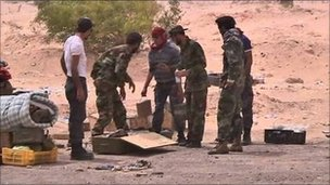 Libyan rebels unpack landmines before laying them near Ajdabiya, 17 April