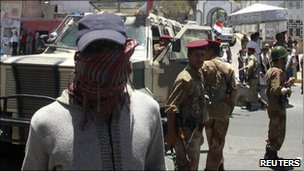 A protester walks past an army barrier in the southern city of Taiz, Yemen, 19 April, 2011