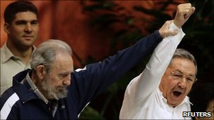 Former Cuban leader Fidel Castro (L) holds up the arm of his brother, Cuba's President Raul Castro, during the closing ceremony of the sixth Cuban Communist Party (PCC) Congress in Havana, 19 April 2011