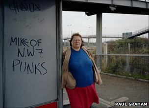 Woman at Bus Stop, Mill Hill, North London, November 1982, from the series A1 - The Great North Road, Vintage colour coupler print