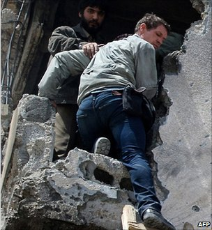 Tim Hetherington being helped from a battle-scarred building in Misrata (20 April 2011)