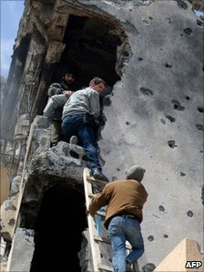 Tim Hetherington (centre) is assisted by Libyan rebels as he climbs down a building in Misrata on 20 April 2011
