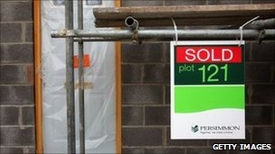 "Home under construction with Persimmon ""sold"" sign in front"
