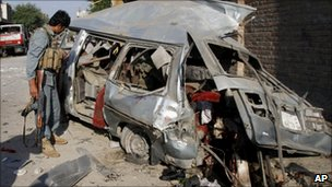 An Afghan police official near the damaged vehicle at the site of the explosion in Jalalabad on 21 April 2011