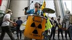 A protester in front of a Tepco showroom
