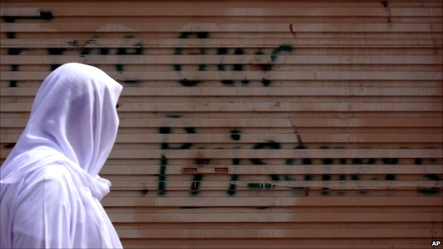 Bahraini man passes graffiti partly painted over by authorities calling for the release of people detained during an anti-government uprising in Bahrain