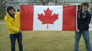 Two students holding the Canadian flag