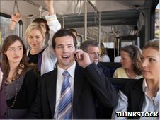 A man on a phone on a crowded bus