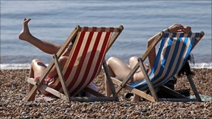 People enjoy the sunshine on the beach in Brighton, southern England