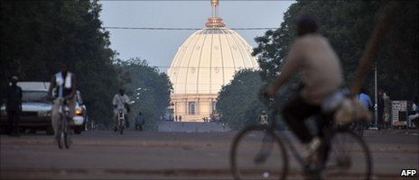 The dome of the Notre Dame de la Paix is seen in the background as a man rides a bicycle in the streets of Yamoussoukro - Archive shot 2010