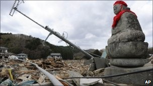 A statue of the guardian of children sits among the rubble at Ishinomaki