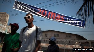 Haitians passing election banner, March 2011