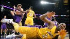 Robin Lopez of the Phoenix Suns secures a rebound while superstar guard Kobe Bryant of the Los Angeles Lakers hits the deck. photo courtesy: Los Angeles Times