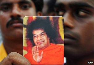 A devotee holds a picture of the late Sri Satya Sai Baba in Puttaparthi, India, 24 April