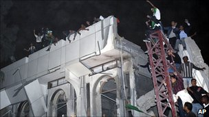 Supporters of Col Gaddafi on a bomb-damaged building. 25 April 2011
