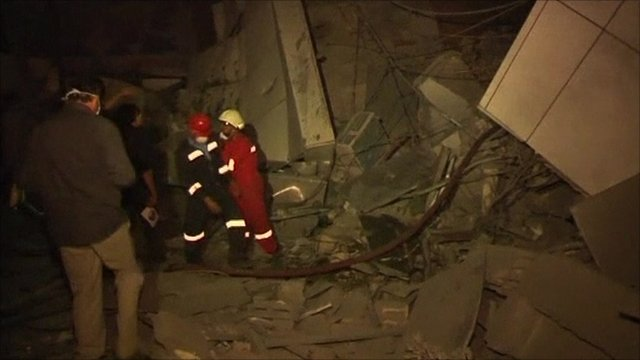 Rescue workers walk at site of Nato attacks in Tripoli