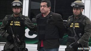 Joaquin Perez, a suspected Farc rebel is escorted by policemen after his arrival at Bogota police on 25 April, 2011