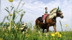 A woman wearing traditional Bavarian clothes takes part in the St George Ride, southern Germany.