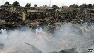 A man douses the still smouldering grain at Kafanchan central market on April 25, 2011 in Kaduna, northern Nigeria
