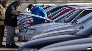 Prospective car-owners check new vehicles at a sales yard in Beijing (file image)