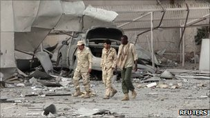 Libyan soldiers walk through ruins in Tripoli